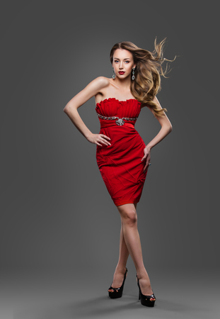 Moda Modelo de pelo ondeando en el viento, joven posando en el estudio Gray, Red Dress Foto de archivo
