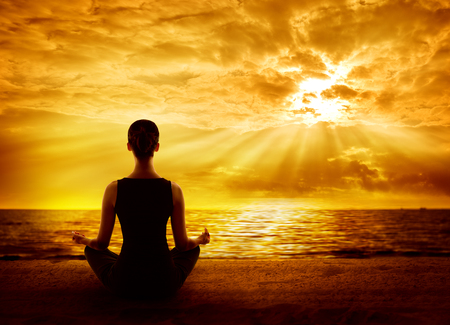 Yoga Meditating Sunrise, Woman Mindfulness Meditation on Beach, Back View photo