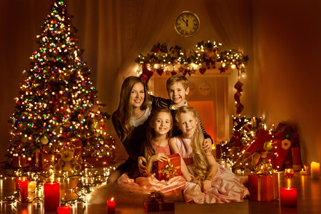 christmas present box: Christmas Family in Decorated Home Room, Xmas Tree Lights, Children Open Present Gift Box