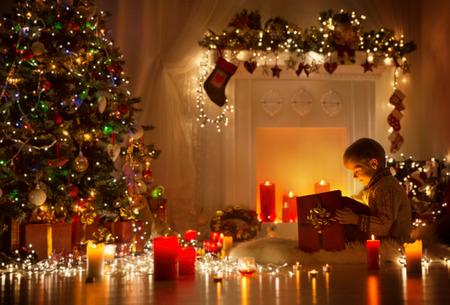 La apertura del niño Regalo de navidad, niño mira a la luz caja de regalo, la noche del sitio del árbol de Navidad y la chimenea