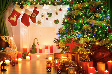 fire place: Christmas Socks Fire Place, Xmas Tree Lights and Fireplace in Decorated Room Interior, Family Stockings Stock Photo