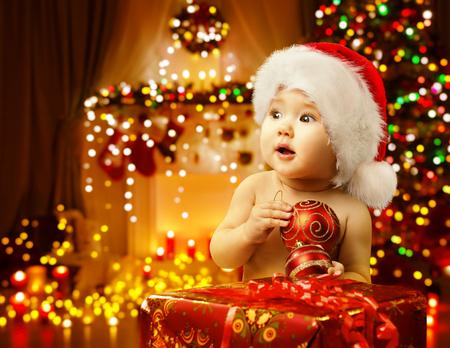 Bébé de Noël Présents d'ouverture, Happy Kid à Santa Hat, Xmas Gift Box, Enfant Looking Side Banque d'images