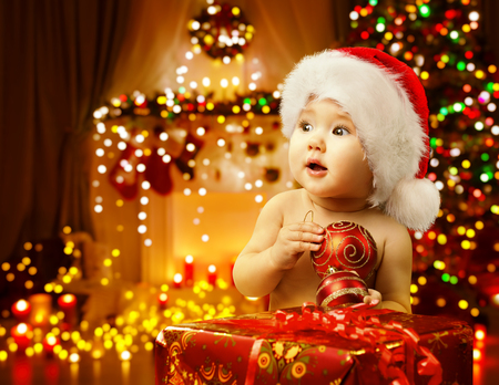 Christmas Baby Opening Present, Happy Kid in Santa Hat, Xmas Gift Box, Child Looking Side