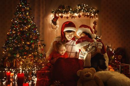 familj: Christmas Family Open Present presentpåse, ser till Magic Light i Xmas Interiör Stockfoto