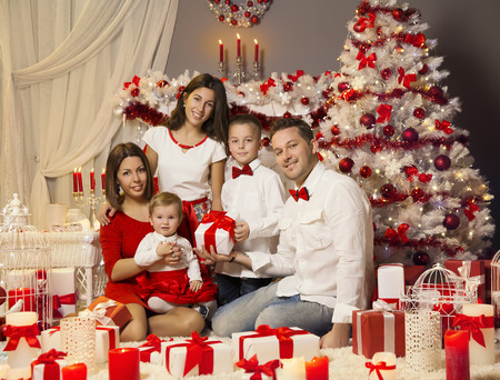 christmas family portrait celebrating in front of xmas tree parents baby children with present