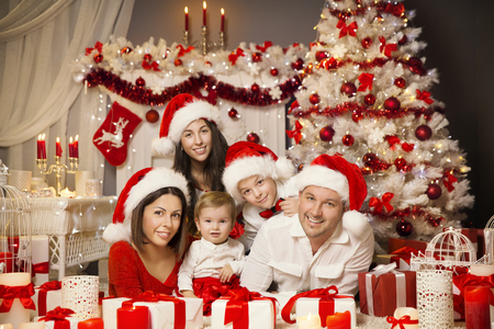 christmas family portrait in room interior xmas tree presents gifts family in red santa