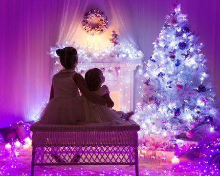 children celebration: Christmas Celebration, Kids Back, Children Looking to Xmas Tree, Magic Lighting Night Interior Stock Photo