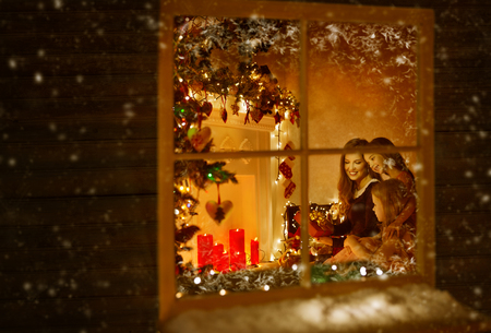 abertura: Ventana de la Navidad, la familia celebra día de fiesta, invierno Nre Año noche, la madre y los niños dentro de la casa Foto de archivo