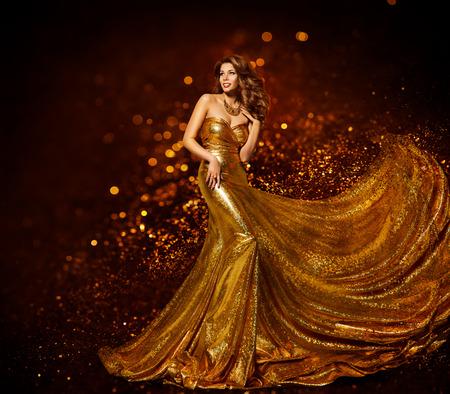 Módní žena Gold Šaty, Luxury Dívka v elegantní zlaté šaty Fabric, Létající Sparkles utěrka Reklamní fotografie