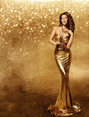 Vestido dorado mujer, Modelo de manera con el champán en el vestido largo de Oro, Vip Niña vacaciones Celebrando sobre el fondo de las chispas Foto de archivo