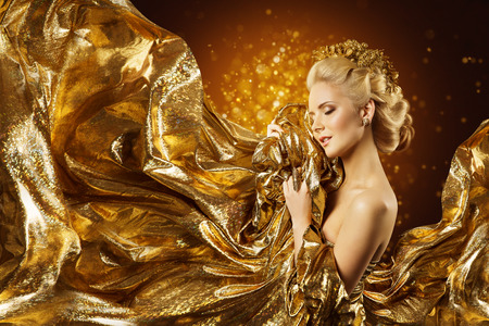 Fashion Model Gold Fabric, Woman Face and Flying Golden Cloth, Girl Beauty Portrait Foto de archivo