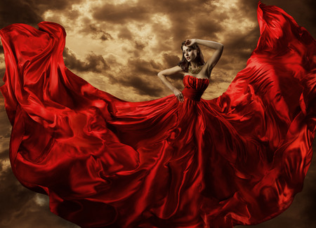 gown: Woman Dancing in Red Dress, Fashion Model Dance with Flying Gown Fabric, Silk Cloth Flowing Waving on wind Stock Photo