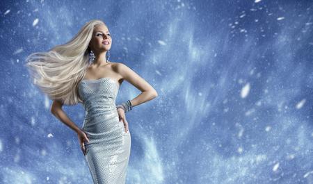 여자 우아한 패션 드레스, 긴 머리 바람에 흔들며, 아름다움 모델 포즈 푸른 겨울 배경 위에 포즈