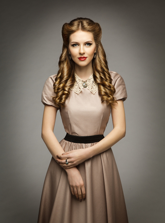 Mujer histórico de estilo victoriano vestido de edad, Bella cortes de pelo rizado, ropa marrón con collar Foto de archivo