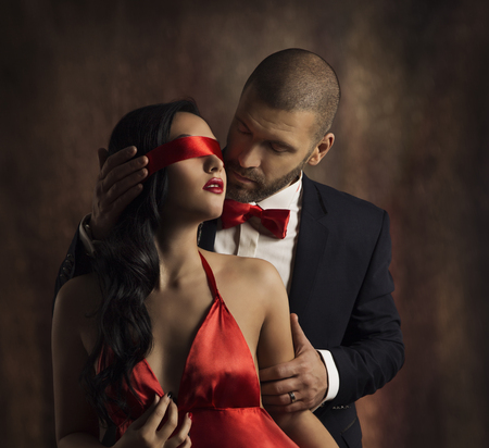 Sexy Couple Love Kiss, Man in Suit Kissing Sensual Woman, Red Fashion Blindfold on Girl Eyes Foto de archivo