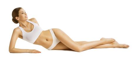 Mujer delgada que la belleza del cuerpo, Modelo hermoso en ropa interior acostada sobre el fondo blanco