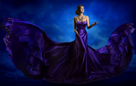 Woman Fashion Dress, Blue Art Gown Flying Silk Fabric, Elegant Model in Waving Purple Cloth Foto de archivo
