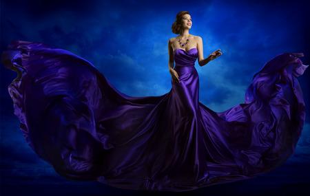 Vestido de la manera de la mujer, vestido de azul Arte del vuelo de la tela de seda, elegante modelo en Agitando paño púrpura Foto de archivo