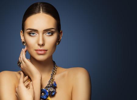 mujer elegante: Maquillaje de la cara de la belleza de la mujer, modelo de moda hermoso maquillan el retrato, señora elegante que toca la piel de la cara, joyería azul Foto de archivo