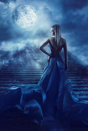 Vrouw klimt Trappen naar Fantasy Moon Hemel, Fairy Girl in Night Blauwjurk, Model Achteraanzicht Kijkend over Schouder Stockfoto