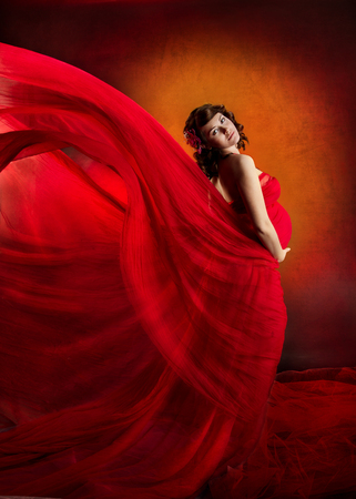 Pregnant woman in red waving flying dress. Looking at camera. photo
