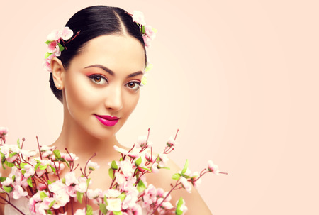 young woman face: Japanese Girl and Flowers, Asian Woman Beauty Makeup, Beautiful Fashion Model with Pink Sakura Flower