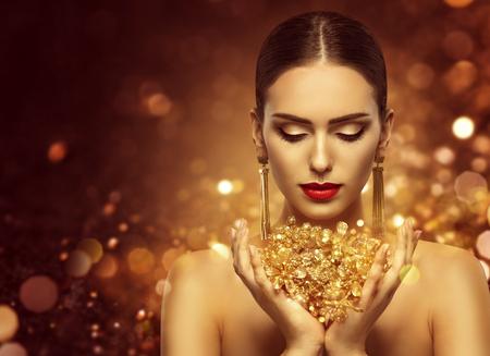 Modello di moda azienda gioielli d'oro in mani, donna bellezza dorata, bella ragazza trucco e gioielli di lusso Archivio Fotografico - 74996779