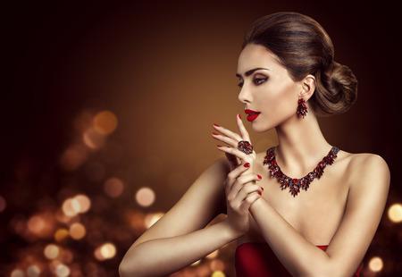 Hairstyle del pelo de la mujer, maquillaje de la belleza del modelo de manera y joyería roja, vista lateral de la muchacha hermosa Foto de archivo