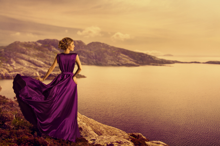 Woman in Elegant Dress on Mountain Coast, Fashion Model in Flowing Gown Cloth, Looking to Landscape View, Outdoor