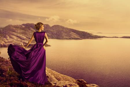 La mujer en el vestido elegante de la Costa Montaña, Modelo de manera en que fluye vestido de tela, Mirando a la opinión del paisaje, al aire libre