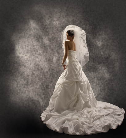Bride in Wedding Dress with Veil, Fashion Bridal Beauty Portrait, Rear View Looking Back over Shoulder, Long Draped Cloth with Folds photo