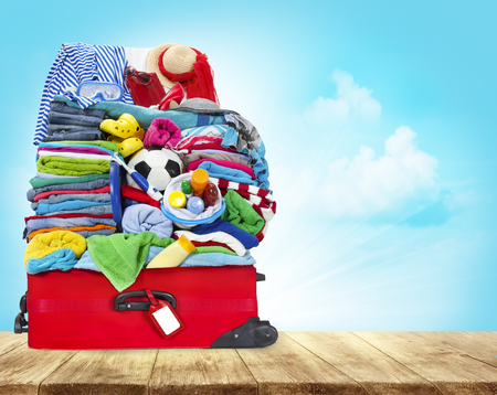 Suitcase Full Of Clothes, Open Luggage with Travel Baggage on Wood Table
