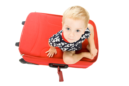 cute child  sitting on the big red suitcase