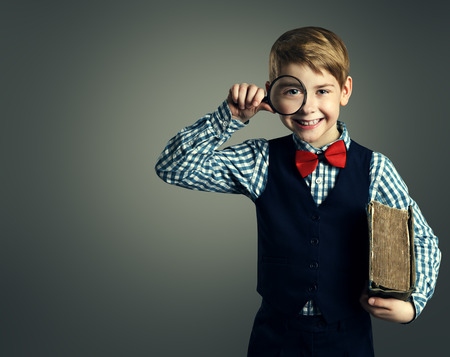 Child with Book and Magnifying Glass, School Kid Education, Happy Student Boy with Magnifier photo