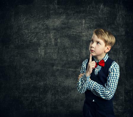 Kid Thinking Over School Blackboard, Child Boy Think Looking Side Finger on Chin, Children Education photo
