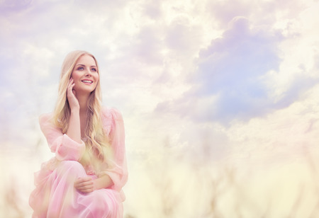 Woman Outdoor Portrait, Happy Girl over Sky Clouds, Smiling Fashion Model in Pink Dress photo