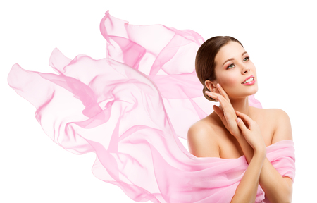 Woman Beauty, Happy Model Face Makeup, Girl looking side away in waving pink fabric, White Background Foto de archivo