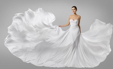 Vrouwelijke witte jurk, Modemodel in lange zijden jurk, Golvende vliegende stof, fladderend op de wind