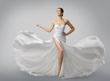 Kobieta biała sukienka, panna młoda modelka w długiej jedwabnej sukni ślubnej, elegancka tkanina latania, fruwające tkaniny Zdjęcie Seryjne