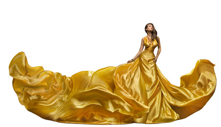 Fashion Model Dress, Woman Dance in Long Gown, Waving Golden Silk Fabric, Beautiful Girl on White Foto de archivo