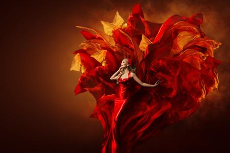 Vestido de arte de mujer, modelo de moda hermoso en vestido rojo artístico, agitando explosión de tela de vuelo