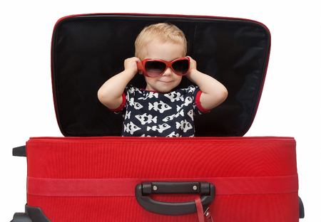 Baby in suitcase, Kid in sunglasses sitting in red luggage. Child isolated over white background
