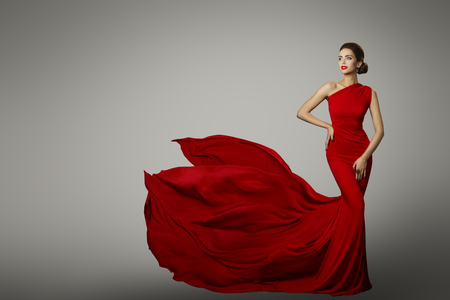 Fashion Model in Red Beauty Dress, Sexy Woman posing evening Gown, Flying Silk Tail over gray background Zdjęcie Seryjne - 87820267