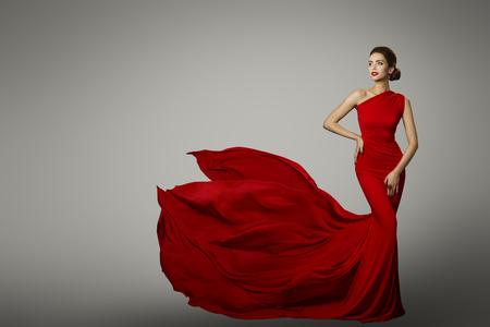 Mannequin en robe de beauté rouge, femme sexy posant robe de soirée, queue de soie volante sur fond gris