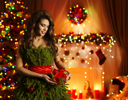 Woman Opening Christmas Present, Model in Xmas Tree Dress Open Gift Box, Decorated New Year Fireplace
