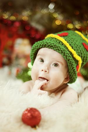 Portrait de bébé, enfant nouveau-né dans le chapeau d'arbre de Noël vert, enfant heureux de quatre mois