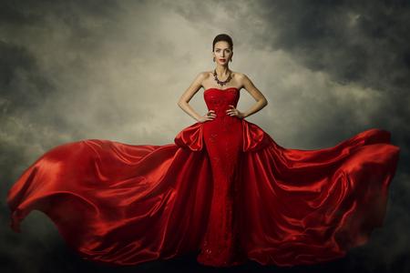 Mode-Modell Art Dress, elegante Frau, die im roten Retro- Kleid, Seidengewebe flattert über Sturm-Himmel-Hintergrund steht Standard-Bild