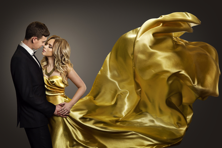 Couple Dancing, Elegant Man and Woman in Fashion Model Gold Dress, Fluttering Gown with Golden Flying Fabric