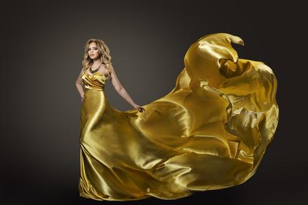 Woman in Gold Dress, Waving Fly Fabric Archivio Fotografico