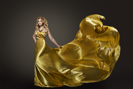 Woman in Gold Dress, Waving Fly Fabric Banque d'images